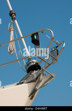 Yacht bow pulpit with navigation lights, jib furling gear and CQR anchor - Stock Photo