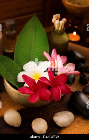 Spa still life setting with aromatic candles, frangipani flower, cold and hot stones. - Stock Photo
