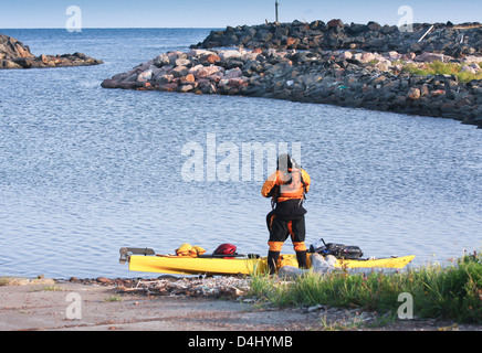 kayak man surfer well equipped and ready for expedition on sea in Cape Breton, , Nova Scotia, Canada - Stock Photo
