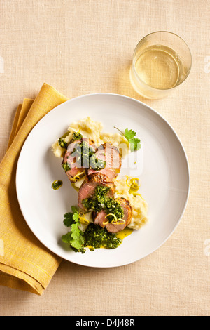 Grilled Pork Tenderloin sliced and served on Potato Puree with Chimichurri sauce. - Stock Photo