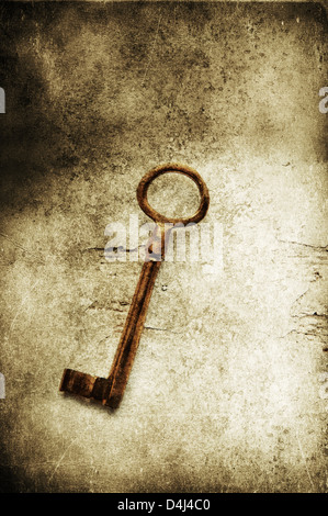 Old brass key on textured background - Stock Photo
