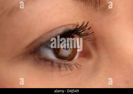 Berlin, Germany, mirroring the Ebay logo at the eye of a woman - Stock Photo
