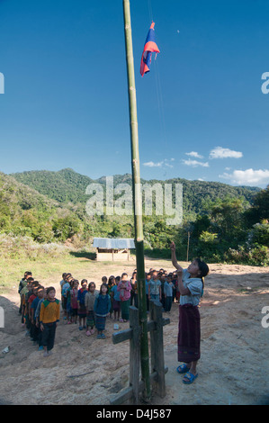 Akha girl performing flag ceremony at a rural school in Phongsaly, Laos - Stock Photo