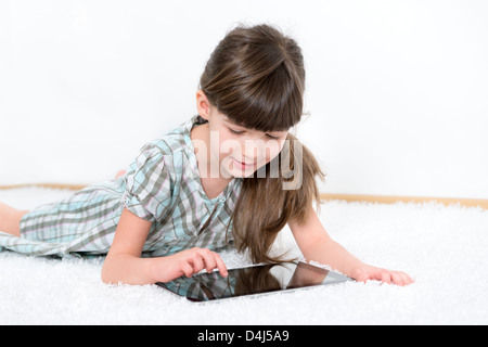 Little girl playing with a modern digital tablet while lying on a white carpet in a white room - Stock Photo