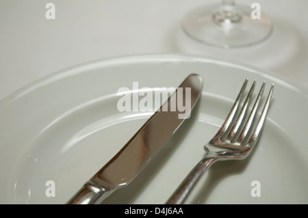 Fork and knife on an empty plate. Close view. - Stock Photo