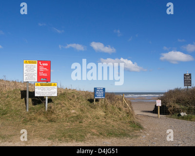 Bilingual danger signs warning of soft sand (quicksand) on Traeth Lligwy beach, Moelfre, Isle of Anglesey, North - Stock Photo
