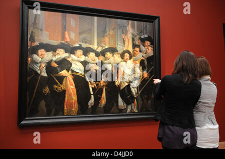Two visitors look at Hendrick Pot?s ?Officers of Cluveniers-Shooter House? (1630) during the exhibition ?Frans Hals - Stock Photo