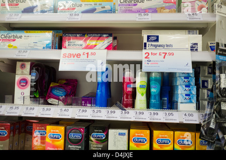 Pregnancy testing kits and condoms on sale in Boots the Chemist pharmacy UK - Stock Photo