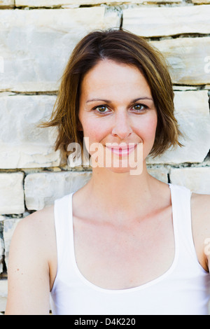 Smiling woman leaning on stone wall - Stock Photo