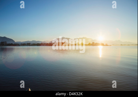 Mountains and sun over still rural lake - Stock Photo