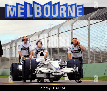 Mechanics of BMW Sauber push back a race car into the pits at the Albert Park Circuit in Melbourne, Australia, 26 - Stock Photo
