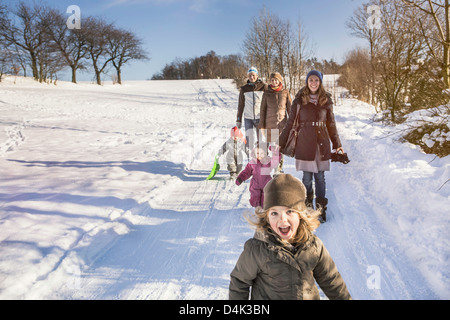 Family walking together in snow - Stock Photo