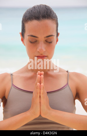 Woman meditating on tropical beach - Stock Photo