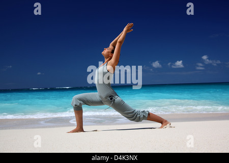 Woman practicing yoga on tropical beach - Stock Photo