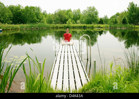 Woman practicing yoga on wooden pier - Stock Photo