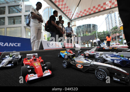 Motor sport fans play with small remote controlled Formula One racing cars on a motor-racing circuit in Kuala Lumpur - Stock Photo