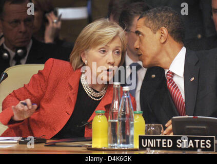 (R) US President Barack Obama talks with US Secretary of State Hillary Clinton (L) during the final conference session - Stock Photo