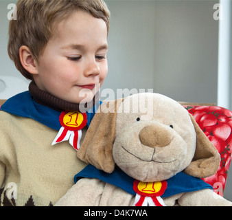 Boy playing with teddy bear - Stock Photo