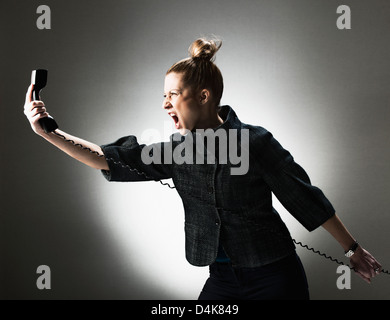 Businesswoman shouting at telephone - Stock Photo