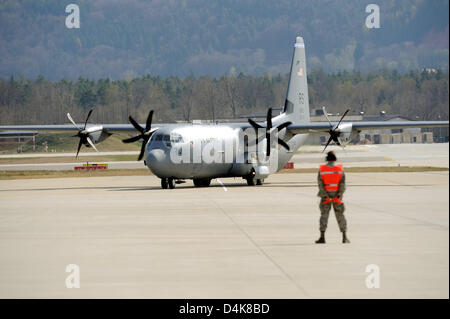 A member of the ground crew directs one of the new transport planes type ?Lockheed Martin C-130J Super Hercules? - Stock Photo