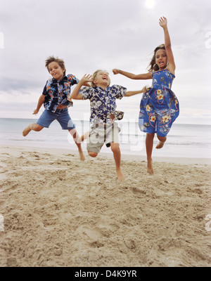 Children jumping together on beach - Stock Photo