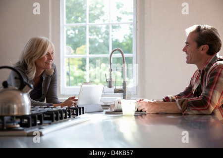 Older couple relaxing in kitchen - Stock Photo