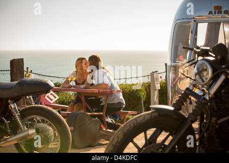 Couple kissing at picnic table outdoors - Stock Photo