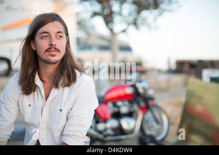 Man sitting outdoors in trailer park - Stock Photo