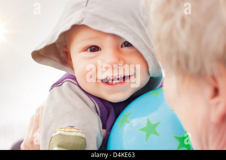 Close up of baby boy's smiling face - Stock Photo