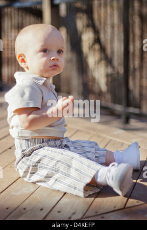 Baby boy sitting on wooden deck - Stock Photo