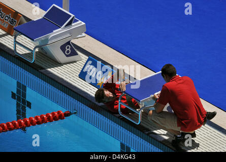 A staff member of time measurement comapny Omega adjusts starting blocks for the upcoming swimming events at the - Stock Photo