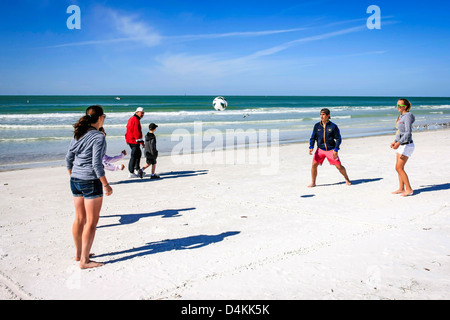 College kids on spring break playing soccer on Siesta Key beach in Florida - Stock Photo