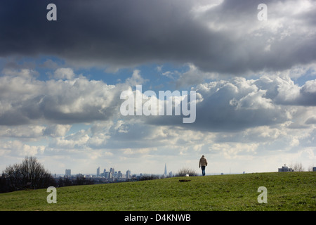 A man walks his dog over the crest of Parliament Hill. - Stock Photo