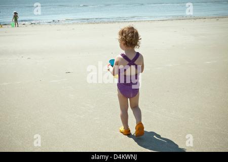 Toddler girl walking on beach - Stock Photo