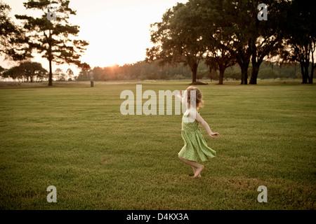 Toddler girl running in grassy field - Stock Photo