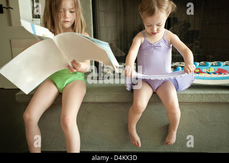 Girls in swimsuits sitting on counter - Stock Photo