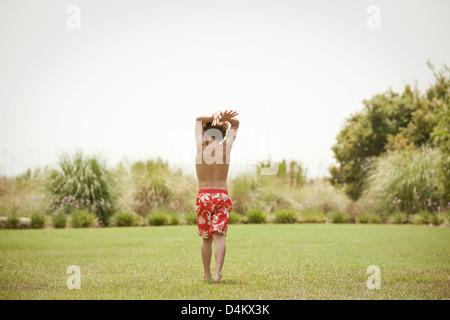 Boy in swimsuit walking in grassy field - Stock Photo