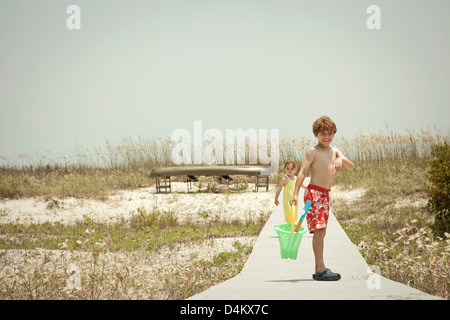 Children on wooden walkway on beach - Stock Photo