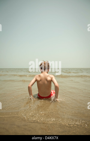 Boy playing in waves on beach - Stock Photo