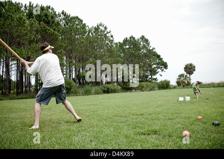 Father and son playing baseball in field - Stock Photo
