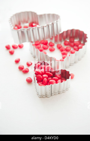 Heart shaped cookie cutters and heart shaped candy - Stock Photo