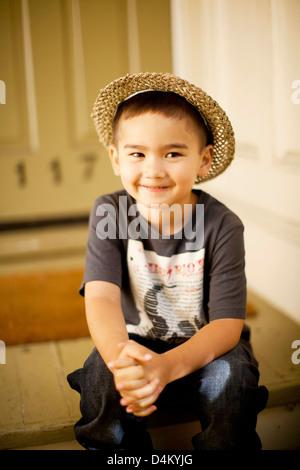 Smiling boy wearing straw hat - Stock Photo