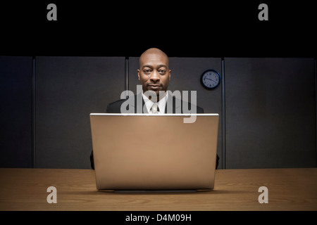 Businessman using laptop in cubicle - Stock Photo