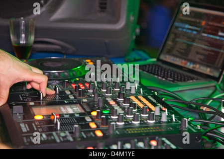 DJ behind the decks in night club - Stock Photo