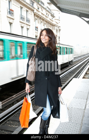 Woman carrying shopping bags on platform - Stock Photo