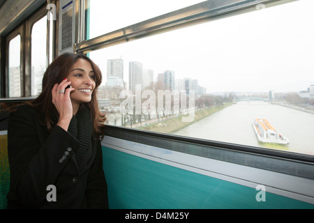 Smiling woman riding train over water - Stock Photo