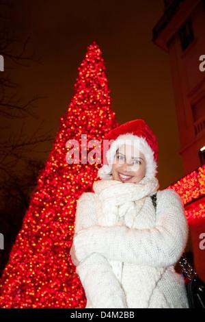 Woman wearing Santa hat on city street - Stock Photo
