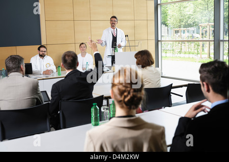 Doctors giving talk in conference room - Stock Photo