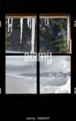 Icicles outside the window of an old cabin in Oregon's Wallowa Mountains. - Stock Photo