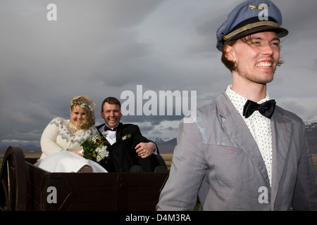 Man driving newlyweds in wooden cart - Stock Photo